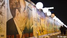 Passanten gehen an der East Side Gallery in Berlin an der Installation Lichtgrenze zum 25-jährigen Mauerfall und dem Gemälde von Dmitri Wladimirowitsch Wrubel vorbei, das den Bruderkuss zwischen Leonid Breschnew und Erich Honecker zeigt. Installation Lichtgrenze zum Jubiläum des Mauerfalls