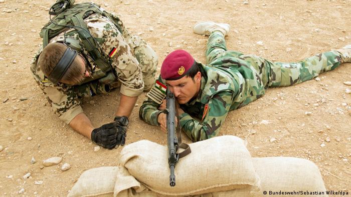 Ein Bundeswehr-Soldat erklärt einem kurdischen Peschmerga die Handhabung eines deutschen Sturmgewehrs, Foto: dpa