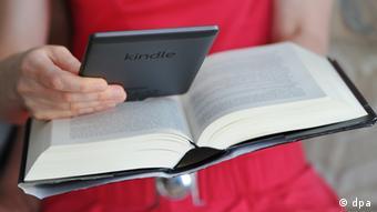 Ein Frau liest gleichzeitig in einem Buch und einem Kindle (Foto: dpa)