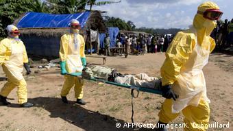 Медики в защитных костюмах переносят больного Эболой