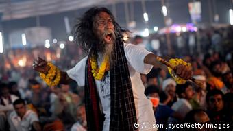 A Baul festival goer, with wild, long, hair and a stick in his hand dances during a live music event.