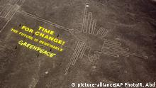 Greenpeace activists stand next to massive letters delivering the message Time for Change: The Future is Renewable next to the hummingbird geoglyph in Nazca in Peru, Monday, Dec. 8, 2014. Greenpeace activists from Brazil, Argentina, Chile, Spain, Germany, Italy and Austria displayed the message, which can be viewed from the sky, during the climate talks in Peru, to honor the Nazca people, whose ancient geoglyphs are one of the country's cultural landmarks. (AP Photo/Rodrigo Abd)