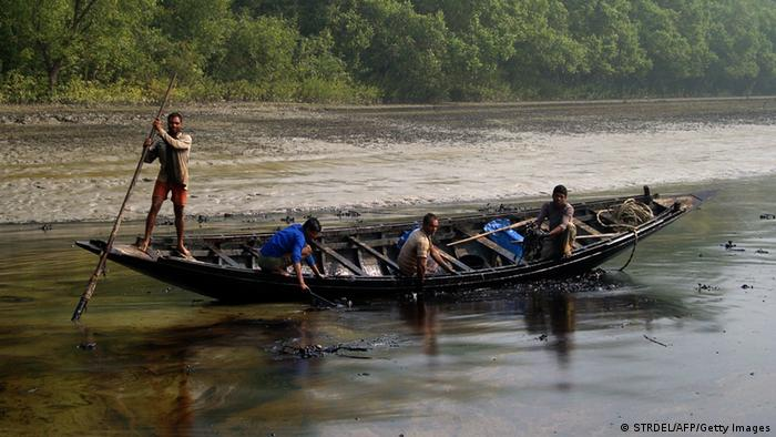 Bangladeshi villagers collect oil from their skiff in the Shela River in Mongla on December 12, 2014, after an oil-tanker carrying 350,000 litres of furnace oil collided with another vessel (Photo: STRDEL/AFP/Getty Images)