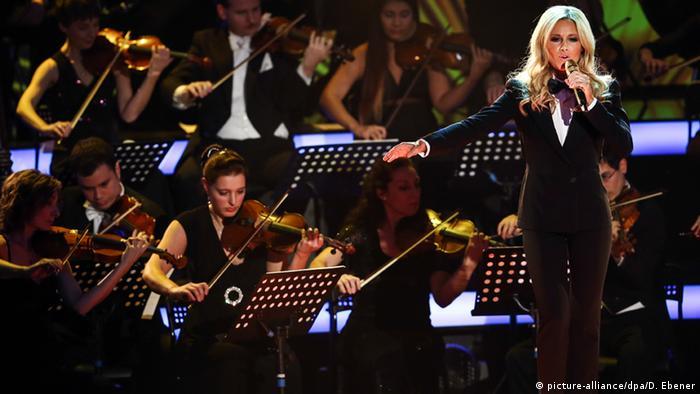 Helene Fischer steht vor einem Streichorchester und singt in ein Mikrofon. (Foto: dpa)