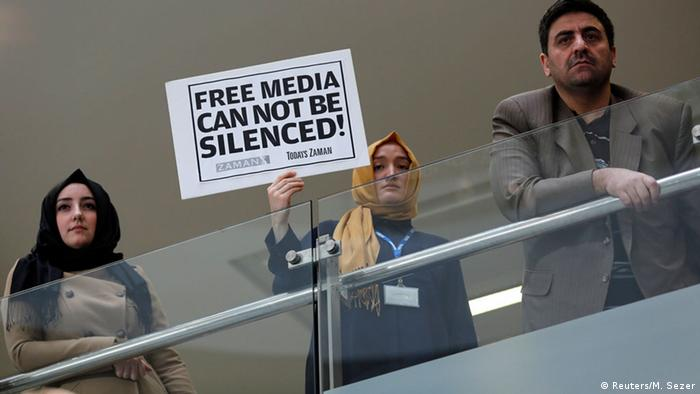 Zaman journalist holds a placard at the headquarters of Zaman daily newspaper. (Photo: REUTERS/Murad Sezer)