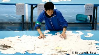 An election official sorts through ballot papers at a counting centre in Tokyo, December 14, 2014 (Photo: REUTERS/Thomas Peter)