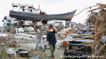 People displaced by the tsunamis, walk amid their ruined neighbourhood on January 4, 2005 in Banda Aceh, Indonesia (Photo: Ulet Ifansasti/Getty Images)