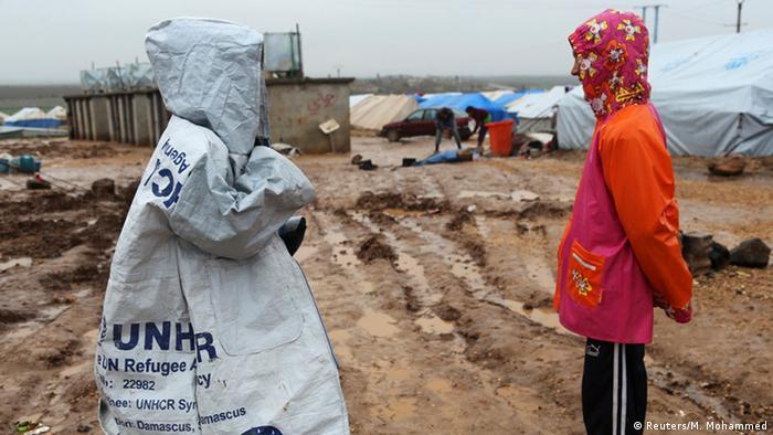 Zwei Kinder, eines trägt einen Mantel mit UNHCR-Emblemen darauf