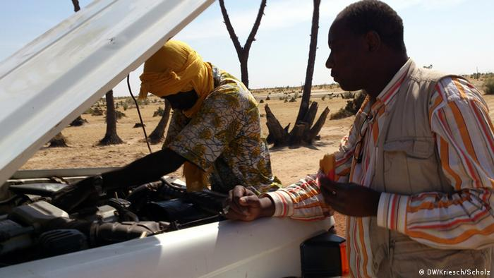 A driver repairing his car engine