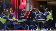 SYDNEY, AUSTRALIA - DECEMBER 15: A person is taken out on a stretcher from the Lindt Cafe, Martin Place following a hostage standoff on December 15, 2014 in Sydney, Australia. Police stormed the Sydney cafe as a gunman had been holding hostages. (Photo by Joosep Martinson/Getty Images)