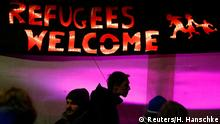 Counter protesters are silhouetted under a banner during a demonstration called by anti-immigration group PEGIDA, a German abbreviation for Patriotic Europeans against the Islamization of the West, in Dresden December 15, 2014. Opponents of Germany's policy towards asylum seekers and Islam took part in the demonstration called by PEGIDA in the eastern German town on Monday. REUTERS/Hannibal Hanschke (GERMANY - Tags: SOCIETY IMMIGRATION POLITICS RELIGION CIVIL UNREST)