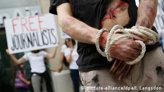 Archive photo, from July 2012: A Reporters Sans Frontieres activist poses, his hands tied with rope and mock injuries on his exposed torso, outside the Iranian embassy in Paris. In the backgrounder, another protester's placard reading Free Journalists is visible.