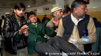 Pakistani volunteers carry a student injured in the shootout at a school under attack by Taliban gunmen, at a local hospital in Peshawar, Pakistan,Tuesday, Dec. 16, 2014 (AP Photo/Mohammad Sajjad)