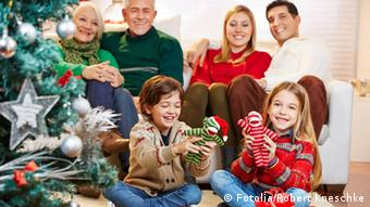 A family gathered around presents under a Christmas tree (Photo: Robert Kneschke - Fotolia.com)