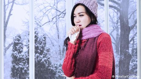 A woman with a cold wears warm winter clothing indoors.