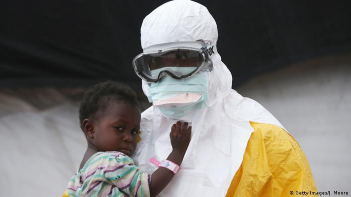 A figure in protective clothing holds a young African child