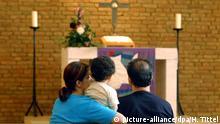 Die Muslime Arezu Almassi (l), Nader Alinea (r) und Tochter Nadaf sitzen vor dem Altar der evangelischen Christen-Kirche in Trier (Foto vom 17.09.2003). In dem Gotteshaus hat die Familie aus dem Iran vor der drohenden Abschiebung aus Deutschland. Die Familie ist seit mehr als sieben Monaten im Kirchenasyl und zur Zeit der einzige Fall von Kirchenasyl in Rheinland-Pfalz. Foto: Harald Tittel/dpa/lrs