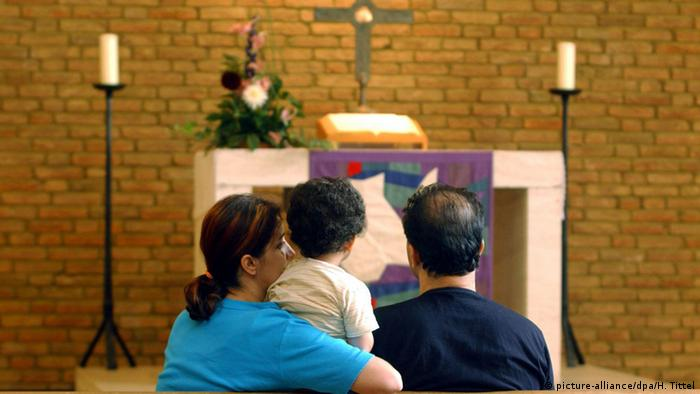 A family sits with their backs to the camera in front of the altar