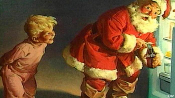 Still aus der Coca Cola-Werbung: Ein Nikolaus holt eine Flasche Cola aus dem Kühlschrank; dahinter steht ein lächelnder blonder Junge. (Foto: DW Camarote.21)