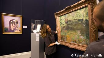 Sotheby's assistants pose with Churchill's 1932 painting of the Goldfish pool at Chartwell