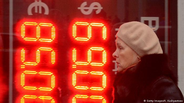 Женщина на фоне табло с валютными курсами