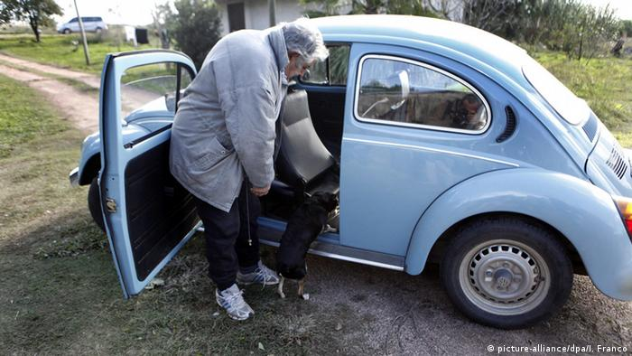 Jose Mujica puts things into his Beetle as ahis dog hops in (picture-alliance/dpa/I. Franco)