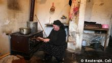 Dile Sherri ,74, kindles fire in her home near Torovice, Lezhe district, northwest of the capital Tirana, December 16, 2014. Torovice served as an internment camp during the former communist regime, and now shelters families coming from the poor northeast region looking for a better life as they move from mountainous areas to more developed zones near urban areas. But these families live in almost dilapidated houses at a former internment camp that sheltered persons opposing the communist regime, and whose family members were taken there as punishment. Up to 100,000 Albanians were executed, imprisoned or sent to internment camps during the four-and-a-half decades of communist rule, which eventually toppled in December 1990 following a students' protest. Sherri said their hopes for a better life have failed, and they still consider themselves as living in an internment camp, unemployed and hardly making ends meet. Picture taken December 16, 2014. REUTERS/Arben Celi (ALBANIA - Tags: POLITICS SOCIETY POVERTY)