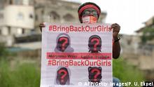 ACHTUNG ARCHIVBILD A supporter of the #BringBackOurGirls campaign carries a placard showing the missing faces of the kidnapped Chibok schoolgirl during a demonstration in the Nigerian capital Abuja on October 14, 2014. Nigerian police on Tuesday blocked supporters of 219 schoolgirls kidnapped by Boko Haram militants from marching on the president's official residence on the six-month anniversary of the abduction. A wall of female officers in full riot gear formed the first line of a barricade in front of less than 100 members of the Bring Back Our Girls campaign, preventing them from setting out.AFP PHOTO/PIUS UTOMI EKPEI (Photo credit should read PIUS UTOMI EKPEI/AFP/Getty Images)