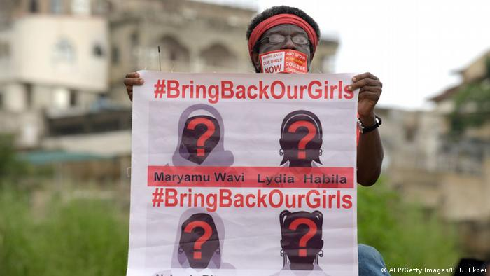 A woman holding a placard for the missing schoolgirls