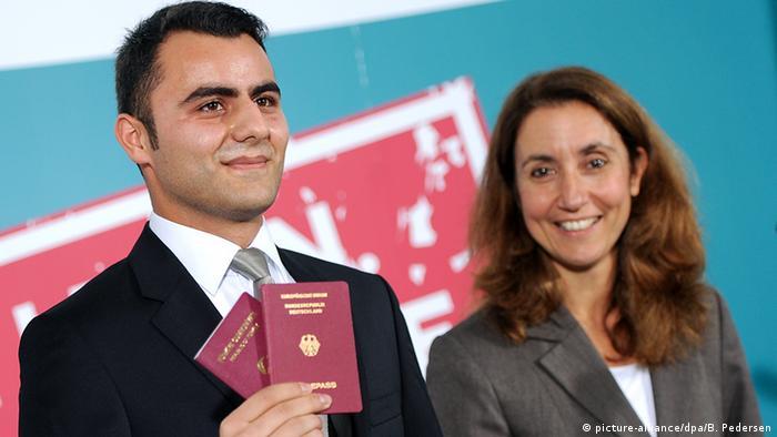 Musa Cakilli shows off his two passports as Integration Minister Aydan Özoguz looks on (Photo: Britta Pedersen/dpa)