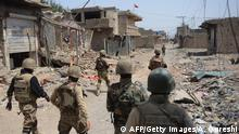 Bildunterschrift:Pakistani soldiers patrol beside destroyed houses during a military operation against Taliban militants in the main town of Miranshah in North Waziristan on July 9, 2014. Last month Pakistan's military launched a long-awaited offensive in North Waziristan, aimed at wiping out longstanding militant strongholds in the area, which borders Afghanistan. More than 800,000 people have fled a major military offensive against the Taliban in a Pakistani tribal area, officials said Wednesday. AFP PHOTO/Aamir QURESHI (Photo credit should read AAMIR QURESHI/AFP/Getty Images)