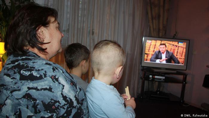 Женщина с детьми смотрит телевизор