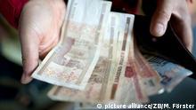 Ein Mann zeigt Weißrussische Rubel