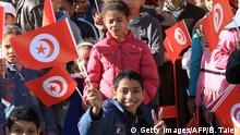 Bildunterschrift:Tunisians wave flags to mark the 4th anniversary of the Tunisian revolution during a campaign rally by President and candidate for the presidential elections, Moncef Marzouki in Sidi Bouzid on December 17, 2014. Tunisians vote in the second round of a presidential election on Sunday, capping off four years of a sometimes chaotic transition since their country sparked the Arab Spring. Incumbent Moncef Marzouki faces political veteran Beji Caid Essebsi in the vote -- the first time Tunisians will be allowed to freely elect their president since independence from France in 1956. AFP PHOTO / BECHIR TAIEB (Photo credit should read BECHIR TAIEB/AFP/Getty Images)