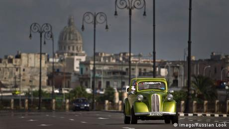 An old fashioned car driving along a boulevard in Havana, Cuba.