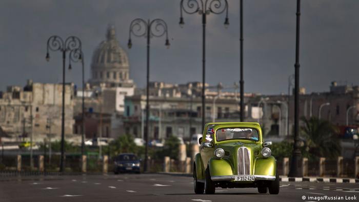 An old fashioned car driving along a boulevard in Havana, Cuba.