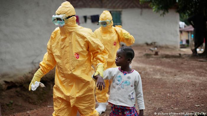 Медики ведуть дівчинку з ознаками захворювання на Еболу. Ліберія
