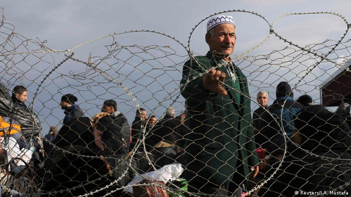 A figure stands behind barbed wire