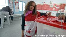 A Tunisian woman wearing the national flag casts her vote on December 21, 2014 at a polling station Ariana near Tunis. The second round vote pits 88-year-old favourite Beji Caid Essebsi, leader of the anti-Islamist Nidaa Tounes party, against incumbent Moncef Marzouki, who held the post through an alliance with the moderate Islamist movement Ennahda. AFP PHOTO / FETHI BELAID (Photo credit should read FETHI BELAID/AFP/Getty Images)