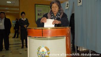 Узбекская женщина бросает бюллетень в избирательную урну