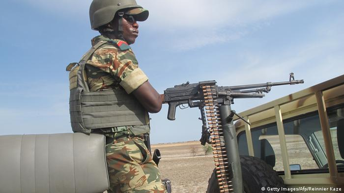 A Cameroonian soldier with an automatic weapon stands on top of a military va