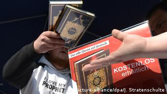 Photo: Man handing over a Quran to another person in Hannover in 2012