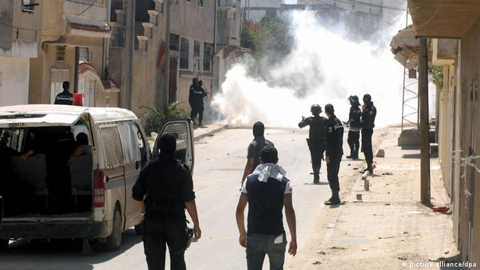 Tunisian riot police forces fire tear gas during clashes with supporters of Islamist group Ansar al-Sharia at Hai al Tadamon in Tunis, Tunisia, 19 May 2013 (Photo: EPA/STR)