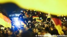 Participants hold German national flags during a demonstration called by anti-immigration group PEGIDA, a German abbreviation for Patriotic Europeans against the Islamization of the West, outside Semperoper opera house in Dresden December 22, 2014. Several thousands opponents of Germany's policy towards asylum seekers and Islam are expected to attend the protest in the eastern German town on Monday. REUTERS/Hannibal Hanschke (GERMANY - Tags: CIVIL UNREST POLITICS)