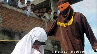Eine Frau erhält Stockschläge als öffentliche Bestrafung in Banda Aceh (Foto: dpa)