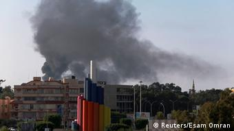 Black smoke billows in the sky above areas where clashes are taking place in Benghazi