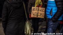 Bei einer Teilnehmerin einer Demonstration gegen Rechtsextremismus, Fremdenhass und die Anti-Islam-Bewegung Pegida am 22.12.2014 in München (Bayern) ist ein Schild mit der Aufschrift REFUGEES WELCOME (Flüchtlinge willkommen) am Rucksack befestigt. Foto: Nicolas Armer/dpa