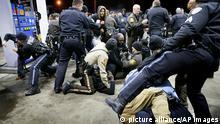 La policía trata de controlar a la multitud, el 24 de diciembre de 2014, en una gasolinera tras un tiroteo en Berkeley, Missouri. Un policía mató el martes a un hombre que sacó un arma y le apuntó en Berkeley, Missouri, según la policía del condado de Saint Louis. (APFoto/St. Louis Post-Dispatch, David Carson)