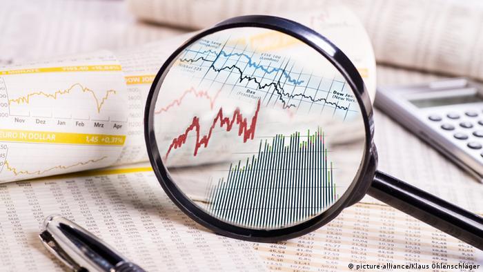 Symbolbild Lupe mit Aktienkursen auf Papieren mit Kurstabelle