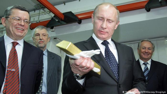 Владимир Путин с золотым слитком в руках